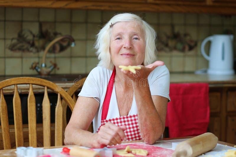 Ευτυχής ανώτερη γυναίκα που κατασκευάζει τα μπισκότα στην κουζίνα στοκ φωτογραφία με δικαίωμα ελεύθερης χρήσης