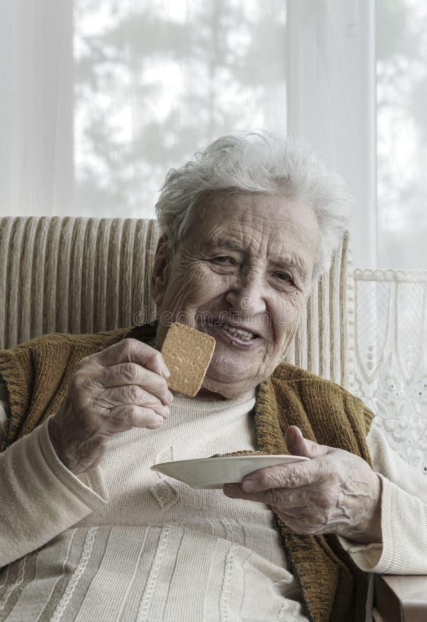 Ευτυχής ανώτερη γυναίκα που τρώει τα μπισκότα στοκ φωτογραφία