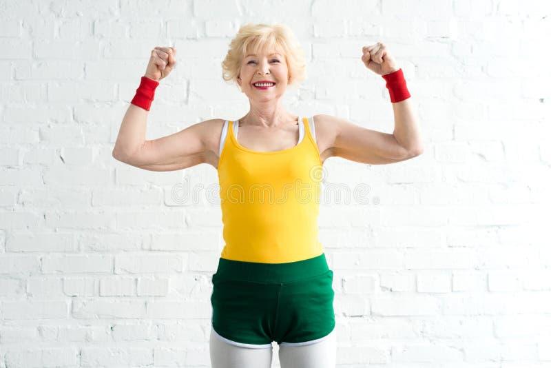 ευτυχής ανώτερη γυναίκα sportswear που παρουσιάζει τους μυς και χαμόγελο στοκ φωτογραφίες με δικαίωμα ελεύθερης χρήσης