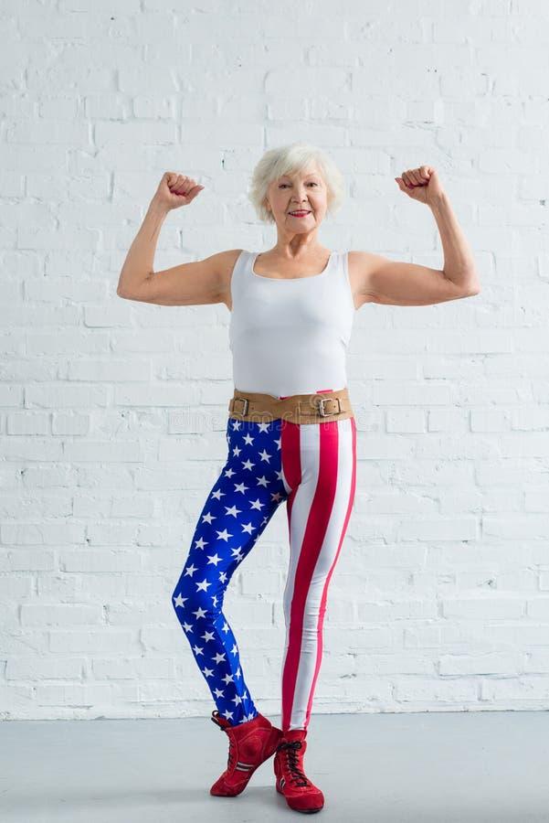 ευτυχής ανώτερη γυναίκα sportswear που παρουσιάζει τους μυς και χαμόγελο στοκ φωτογραφίες
