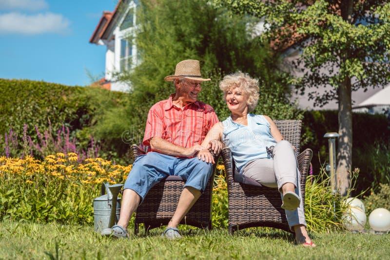 Ευτυχής ανώτερη ερωτευμένη χαλάρωση ζευγών μαζί στον κήπο το καλοκαίρι στοκ εικόνες