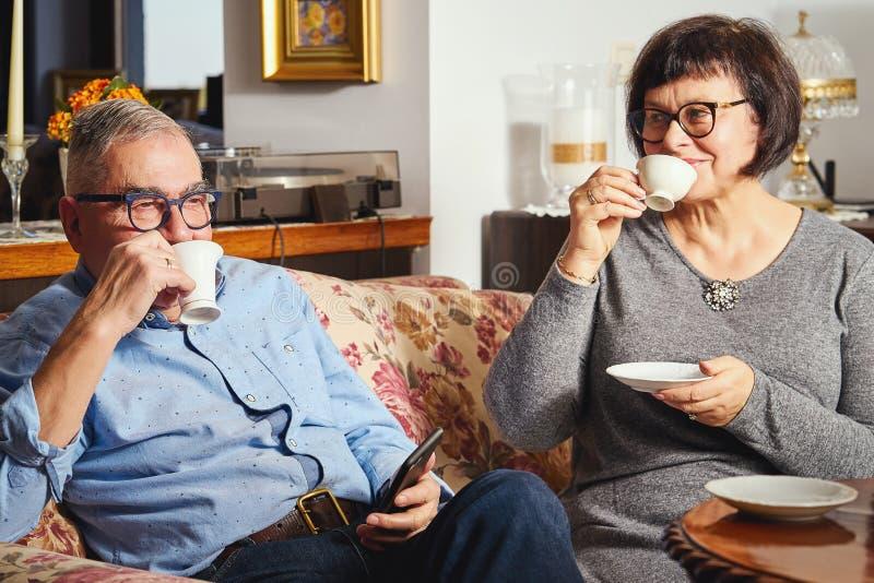 Ευτυχής ανώτερη συνεδρίαση ζευγών στον καναπέ και απόλαυση του καφέ και του τσαγιού στοκ εικόνες