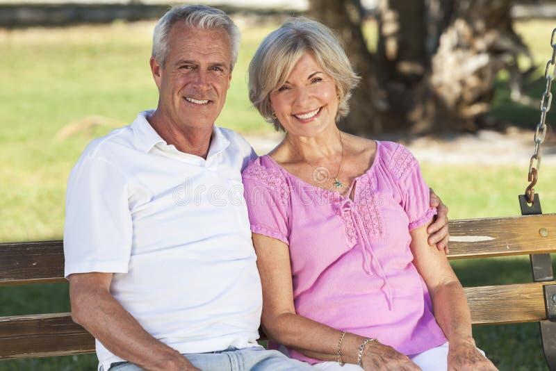 Ευτυχής ανώτερη συνεδρίαση ζεύγους στον πάγκο στην ηλιοφάνεια στοκ εικόνες