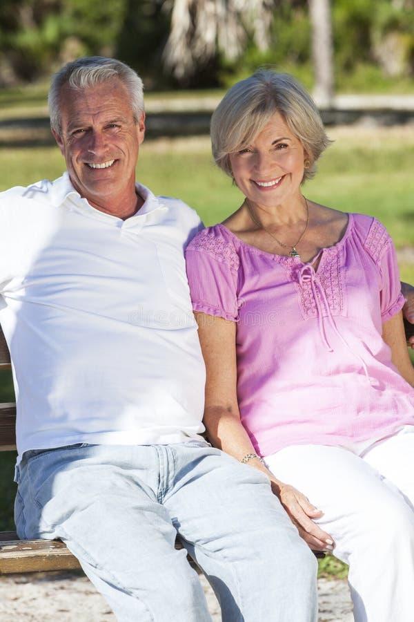 Ευτυχής ανώτερη συνεδρίαση ζεύγους στον πάγκο στην ηλιοφάνεια στοκ φωτογραφίες με δικαίωμα ελεύθερης χρήσης
