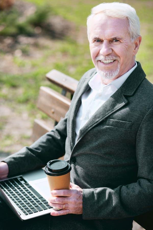 Ευτυχής ανώτερος επιχειρηματίας που απολαμβάνει τον καφέ στοκ φωτογραφίες