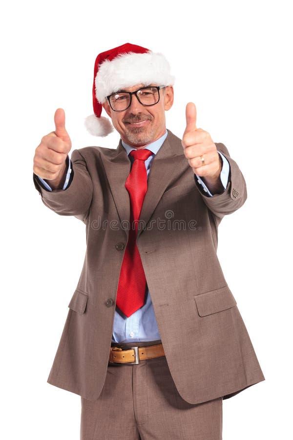 Ευτυχής ανώτερος επιχειρηματίας που φορά το καπέλο Άγιου Βασίλη που κάνει το εντάξει σημάδι στοκ φωτογραφίες με δικαίωμα ελεύθερης χρήσης
