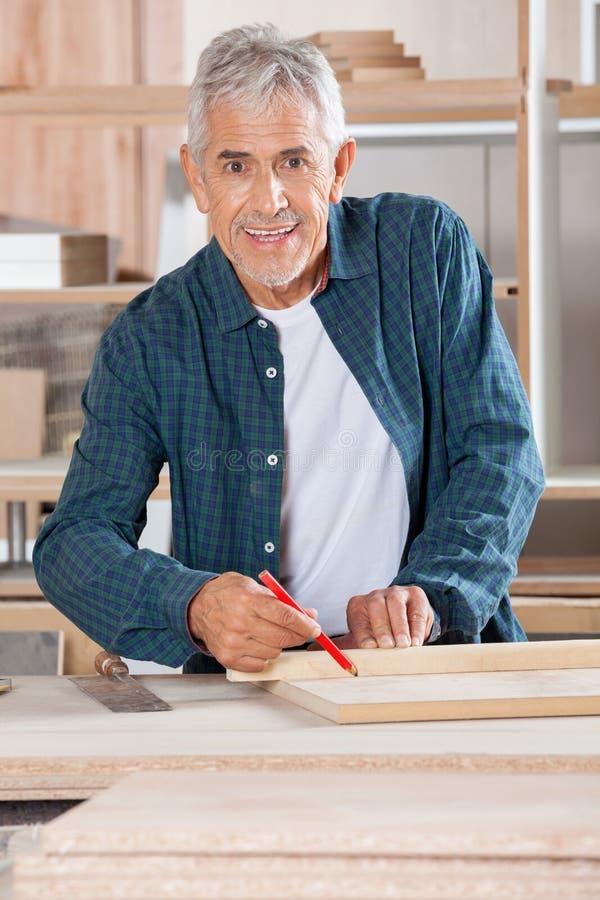 Ευτυχής ανώτερος ξυλουργός που χαρακτηρίζει στο ξύλο με το μολύβι στοκ φωτογραφίες με δικαίωμα ελεύθερης χρήσης