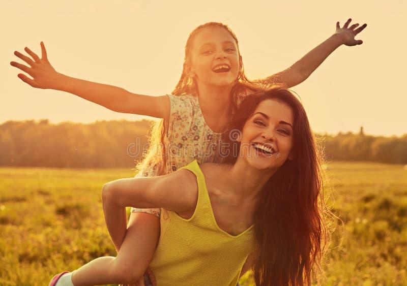Ευτυχής απολαμβάνοντας μητέρα που αγκαλιάζει το εύθυμο γελώντας κορίτσι παιδιών της στο φωτεινό θερινό υπόβαθρο ηλιοβασιλέματος c στοκ εικόνες