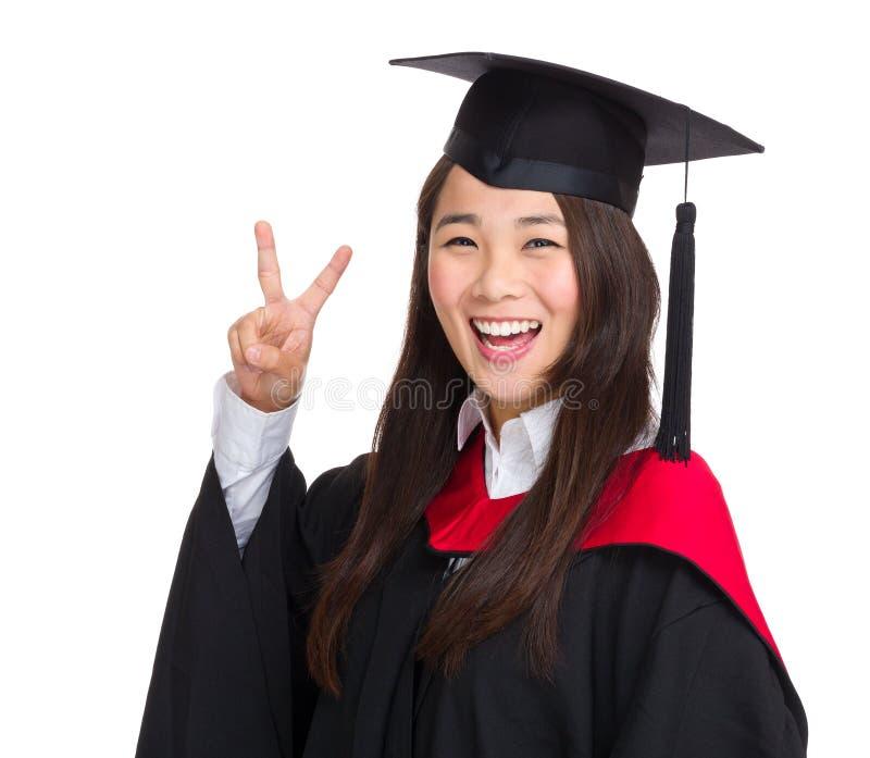 Ευτυχής απόφοιτος φοιτητής της Ασίας με το σημάδι νίκης στοκ εικόνα