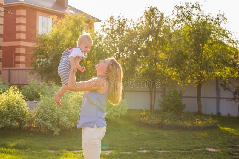 Ευτυχής αρμονική οικογένεια υπαίθρια η μητέρα ρίχνει το μωρό επάνω, που γελά και που παίζει το καλοκαίρι στη φύση στοκ εικόνα