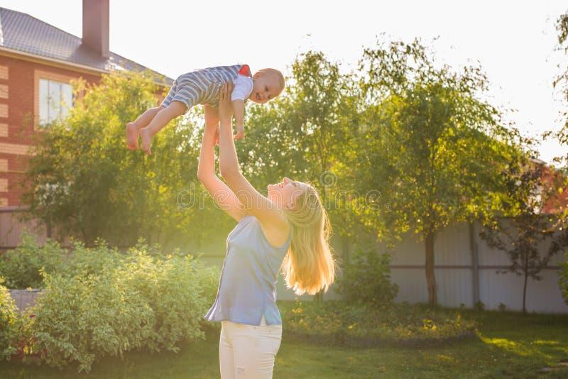 Ευτυχής αρμονική οικογένεια υπαίθρια η μητέρα ρίχνει το μωρό επάνω, που γελά και που παίζει το καλοκαίρι στη φύση στοκ εικόνα με δικαίωμα ελεύθερης χρήσης