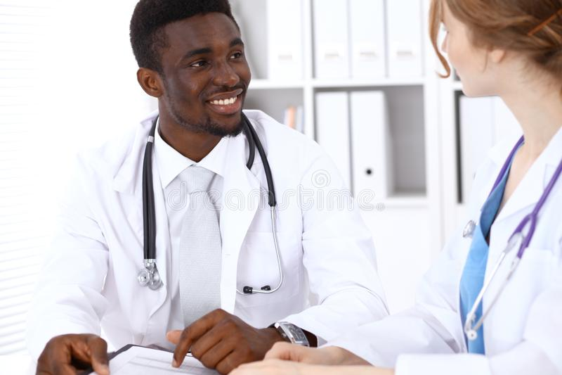 Ευτυχής αρσενικός γιατρός αφροαμερικάνων με το ιατρικό προσωπικό στο νοσοκομείο η έννοια βρίσκεται καθορισμένο στηθοσκόπιο χρημάτ στοκ φωτογραφία