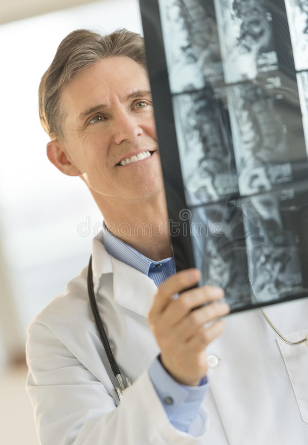 Ευτυχής αρσενικός γιατρός που αναλύει την εικόνα ακτίνας X στοκ φωτογραφία