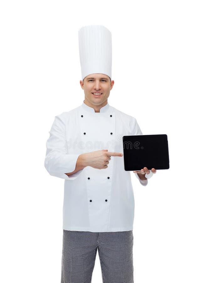 Ευτυχής αρσενικός μάγειρας αρχιμαγείρων που παρουσιάζει με το PC ταμπλετών στοκ εικόνα