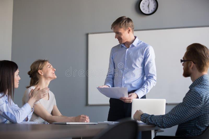 Ευτυχής αρσενικός προϊστάμενος που εγκωμιάζει τους υπαλλήλους που εκτιμούν το καλό αποτέλεσμα εργασίας στοκ εικόνες