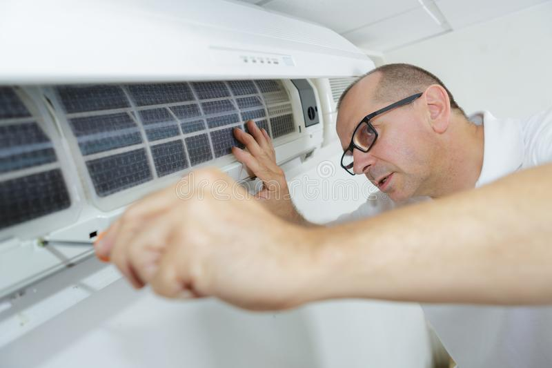 Ευτυχής αρσενικός τεχνικός που επισκευάζει το κλιματιστικό μηχάνημα με το κατσαβίδι στοκ εικόνες