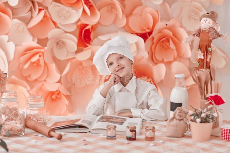 Ευτυχής αρχιμάγειρας αγοριών που στέκεται κοντά στον πίνακα κουζινών στοκ εικόνα