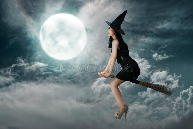 Ευτυχής ασιατική γυναίκα μαγισσών που πετά επάνω από ένα σκουπόξυλο στοκ φωτογραφίες