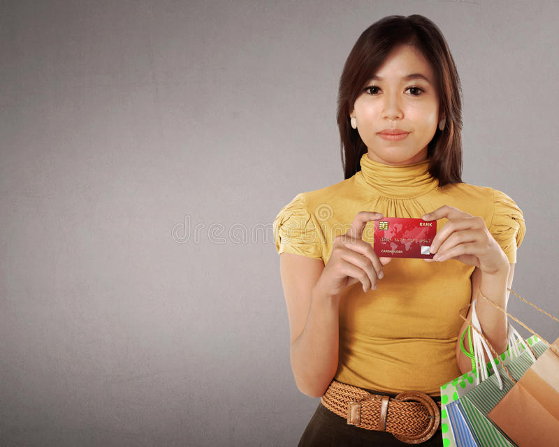 Ευτυχής ασιατική γυναίκα με πολλές τσάντες αγορών και πιστωτική κάρτα σε την στοκ εικόνες