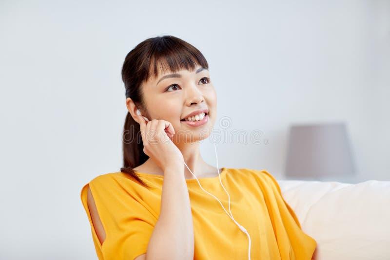 Ευτυχής ασιατική γυναίκα με τη μουσική ακούσματος ακουστικών στοκ φωτογραφίες με δικαίωμα ελεύθερης χρήσης