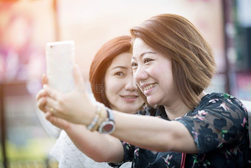Ευτυχής ασιατική γυναίκα με το φίλο που παίρνει ένα selfie στοκ φωτογραφία