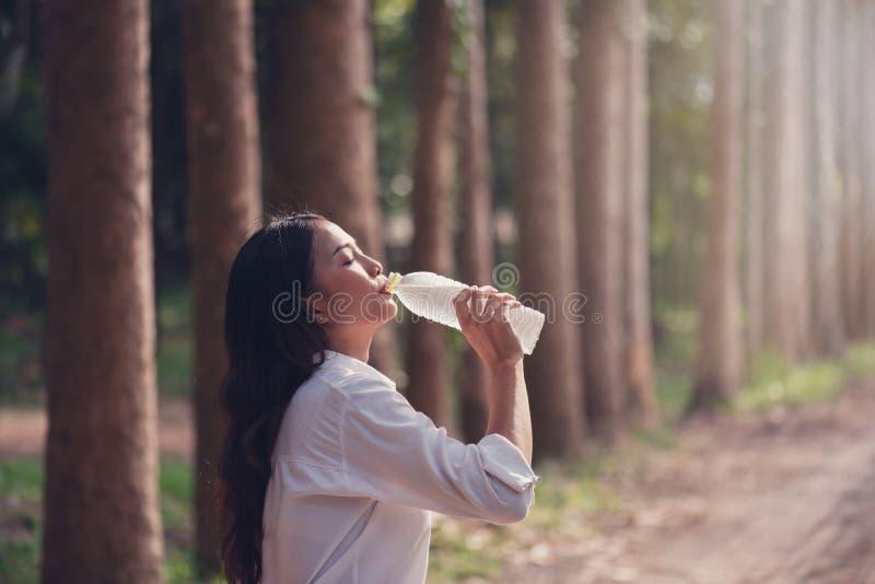 Ευτυχής ασιατική γυναίκα που πίνει το γλυκό νερό στο δάσος στοκ εικόνες