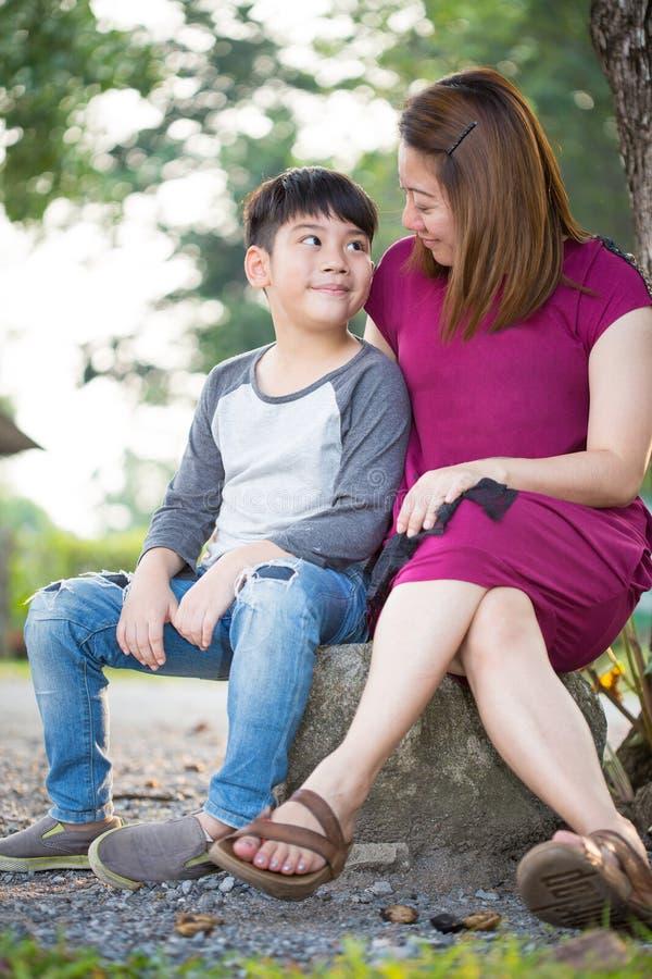 Ευτυχής ασιατική μητέρα με το γιο της στο πάρκο στοκ εικόνα