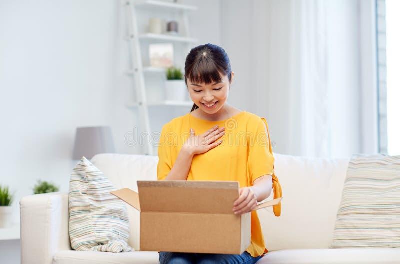 Ευτυχής ασιατική νέα γυναίκα με το κιβώτιο δεμάτων στο σπίτι στοκ εικόνες