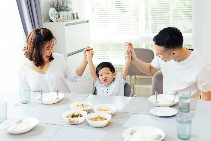 Ευτυχής ασιατική οικογένεια που αυξάνει τα χέρια παιδιών ` s επάνω και που χαμογελά ενώ έχοντας ένα γεύμα από κοινού στοκ φωτογραφίες