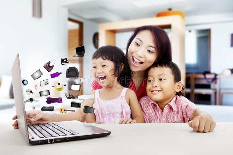 Ευτυχής ασιατική οικογένεια που ψωνίζει on-line στοκ εικόνα με δικαίωμα ελεύθερης χρήσης