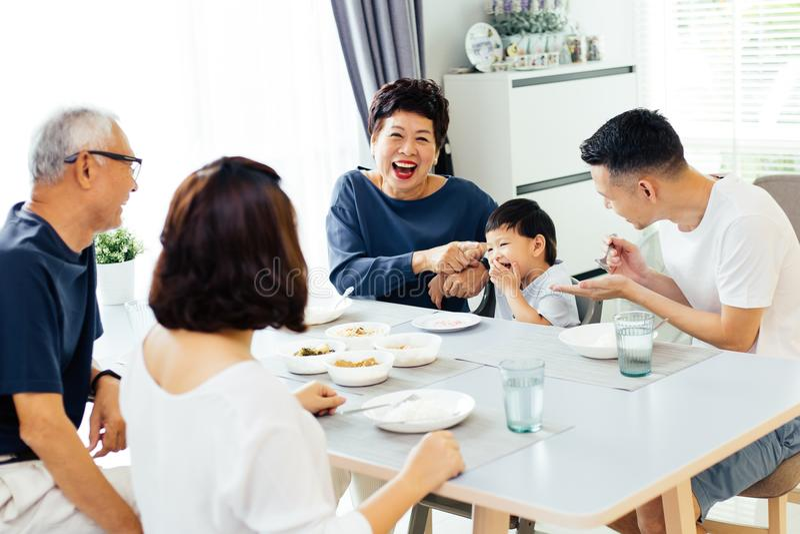 Ευτυχής ασιατική πολυμελής οικογένεια που έχει το σύνολο γευμάτων στο σπίτι του γέλιου και της ευτυχίας στοκ εικόνα