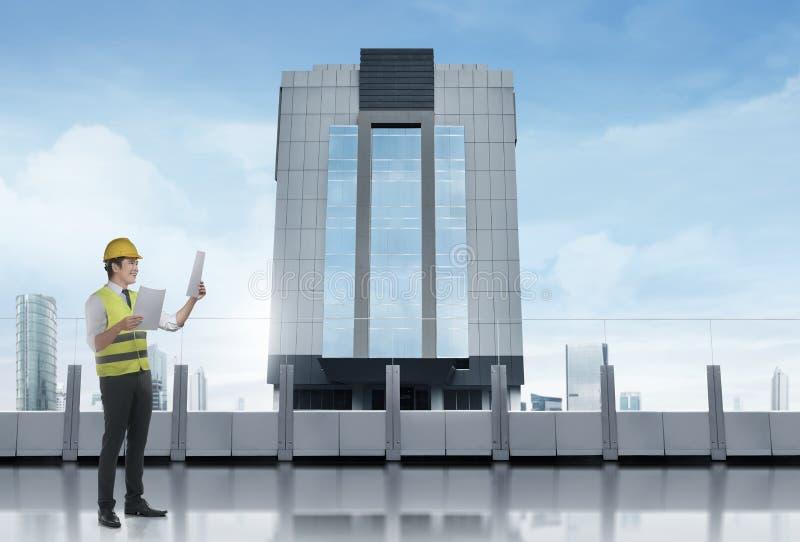 Ευτυχής ασιατικός εργάτης οικοδομών με το σχεδιάγραμμα που στέκεται στο terra στοκ εικόνα με δικαίωμα ελεύθερης χρήσης