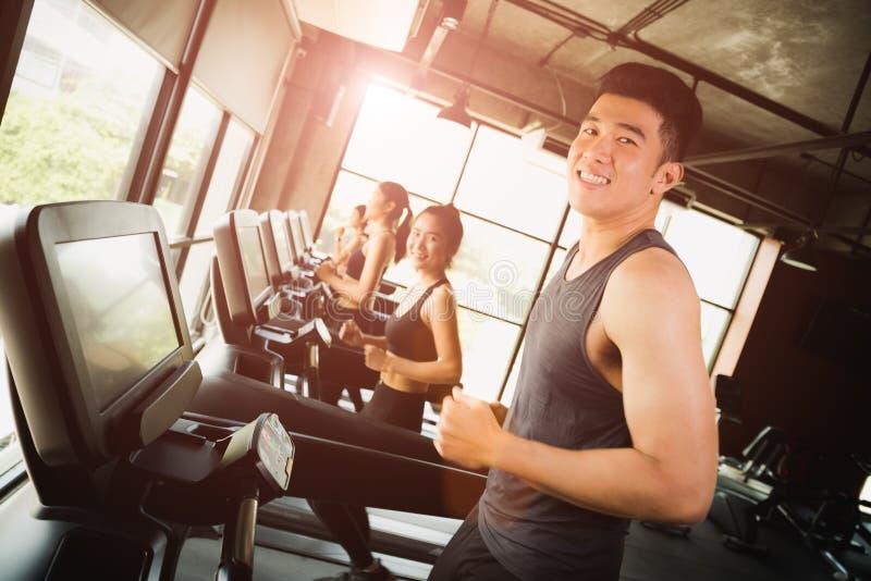 Ευτυχής ασιατικός νεαρός άνδρας με την ομάδα τρεξίματος νέων στοκ φωτογραφίες με δικαίωμα ελεύθερης χρήσης