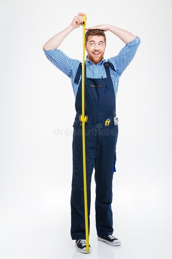 Ευτυχής αστείος νεαρός άνδρας που μετρά το ύψος σωμάτων του που χρησιμοποιεί την ταινία στοκ εικόνες