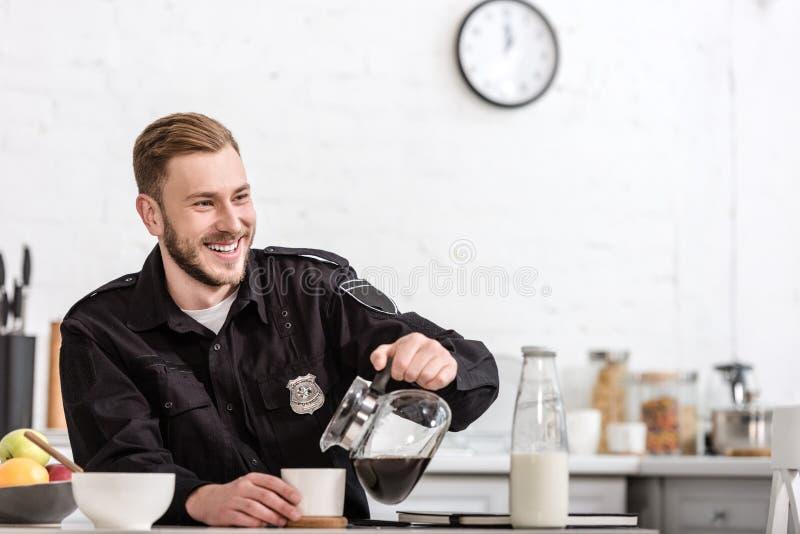 ευτυχής αστυνομικός που χύνει το φιλτραρισμένο καφέ από το δοχείο γυαλιού στοκ εικόνες