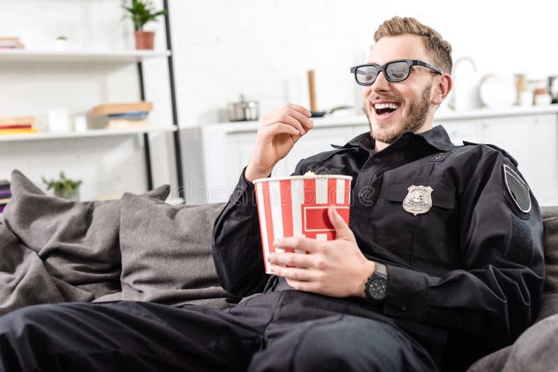 Ευτυχής αστυνομικός στα τρισδιάστατα γυαλιά που κάθεται στον καναπέ, που τρώει popcorn και στοκ εικόνες με δικαίωμα ελεύθερης χρήσης