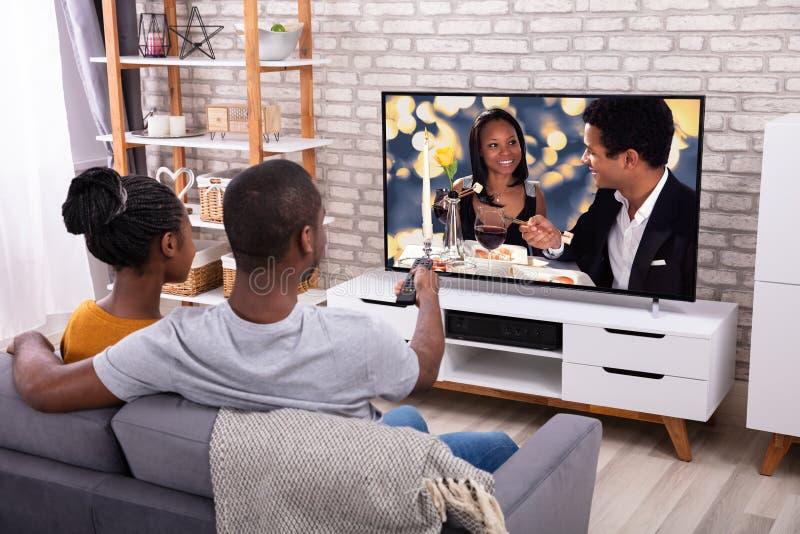 Ευτυχής αφρικανική τηλεόραση προσοχής ζεύγους στοκ εικόνα με δικαίωμα ελεύθερης χρήσης