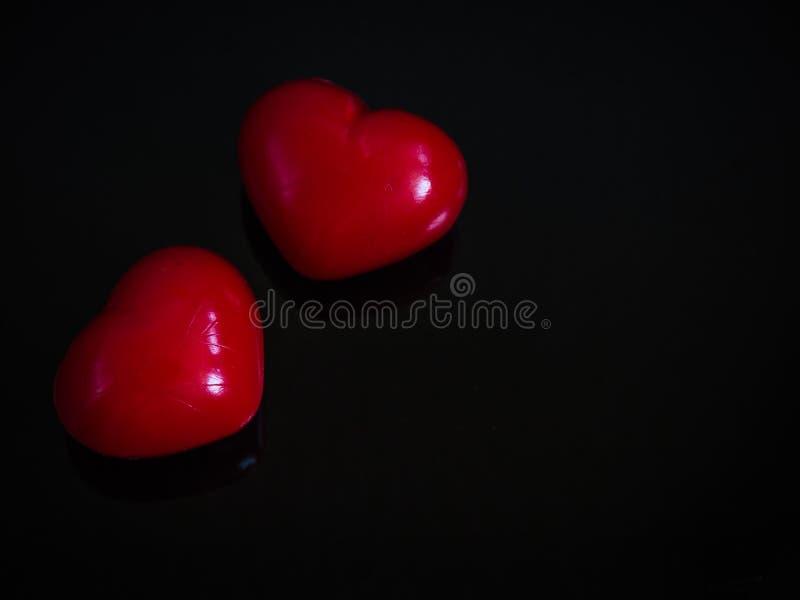 Ευτυχής βαλεντίνος ημέρα δύο κόκκινες καρδιές στο μαύρο υπόβαθρο στοκ φωτογραφίες