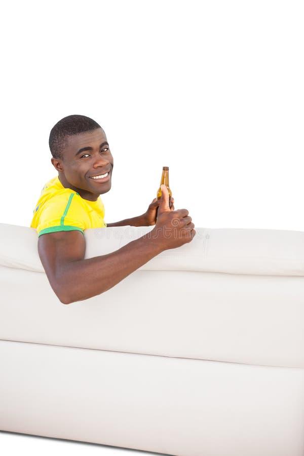 Ευτυχής βραζιλιάνα συνεδρίαση οπαδών ποδοσφαίρου στον καναπέ με μια μπύρα στοκ εικόνα με δικαίωμα ελεύθερης χρήσης