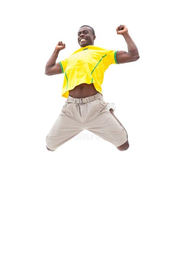 Ευτυχής βραζιλιάνος οπαδός ποδοσφαίρου που πηδά επάνω στοκ φωτογραφία