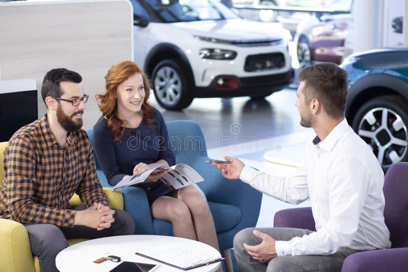 Ευτυχής γάμος που αγοράζει το νέο αυτοκίνητο μιλώντας με τον πωλητή σε ένα dea στοκ φωτογραφία