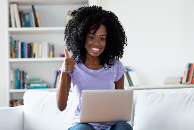 Ευτυχής γελώντας γυναίκα αφροαμερικάνων με τον υπολογιστή στοκ εικόνα