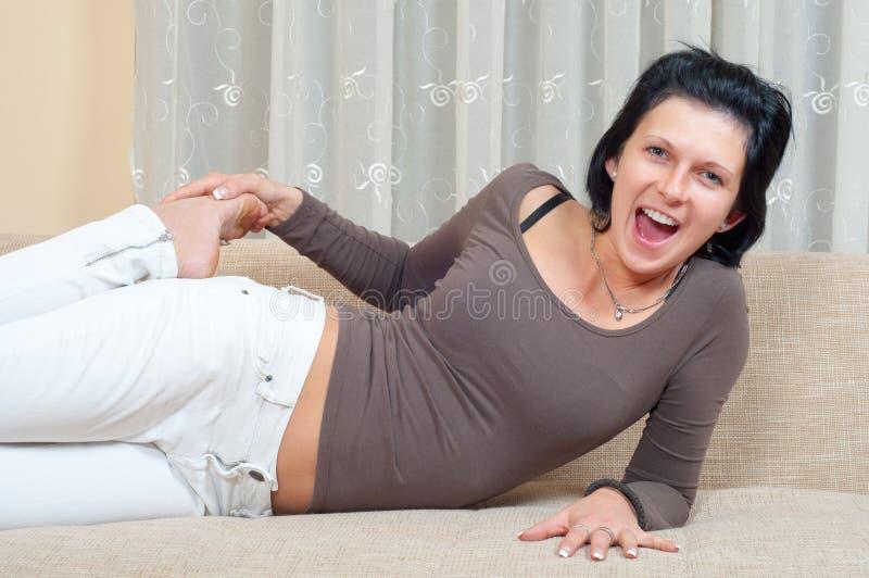 ευτυχής γελώντας να βρεθεί καναπέδων όμορφη γυναίκα στοκ φωτογραφίες