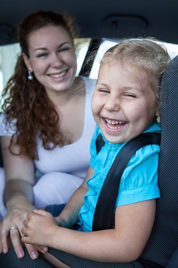 Ευτυχής γελώντας μητέρα με τη μικρή κόρη στο αυτοκίνητο στοκ φωτογραφία