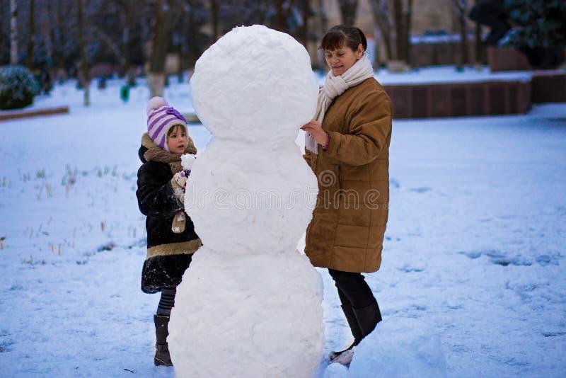 Ευτυχής γιαγιά και λίγη εγγονή sculpt ένας μεγάλος πραγματικός χιονάνθρωπος στοκ φωτογραφίες με δικαίωμα ελεύθερης χρήσης