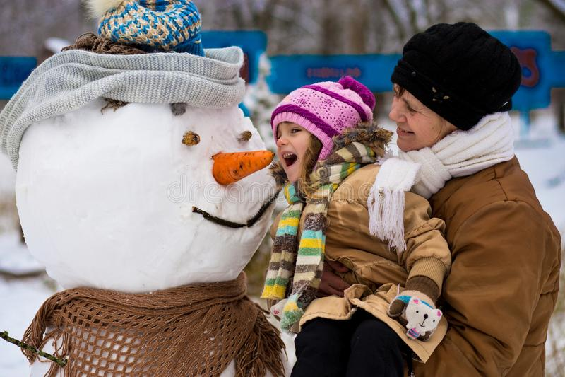 Ευτυχής γιαγιά και λίγη εγγονή sculpt ένας μεγάλος πραγματικός χιονάνθρωπος στοκ φωτογραφίες