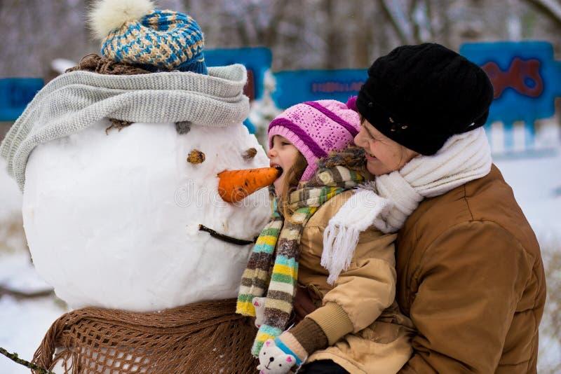 Ευτυχής γιαγιά και λίγη εγγονή sculpt ένας μεγάλος πραγματικός χιονάνθρωπος στοκ εικόνα