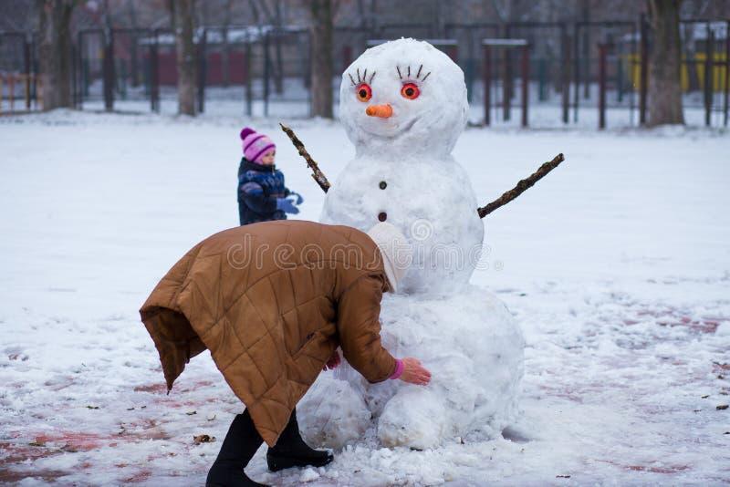 Ευτυχής γιαγιά και λίγη εγγονή sculpt ένας μεγάλος πραγματικός χιονάνθρωπος στοκ εικόνες