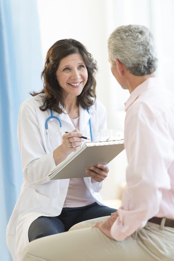 Ευτυχής γιατρός με την περιοχή αποκομμάτων που εξετάζει τον ασθενή στοκ εικόνες