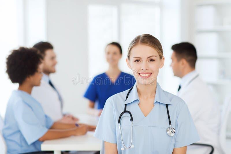 Ευτυχής γιατρός πέρα από την ομάδα γιατρών στο νοσοκομείο στοκ εικόνα